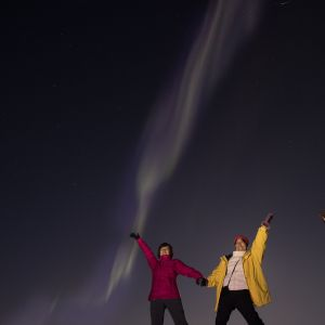 Two people with joining hands other arms up to the sky under the aurora - northern lights